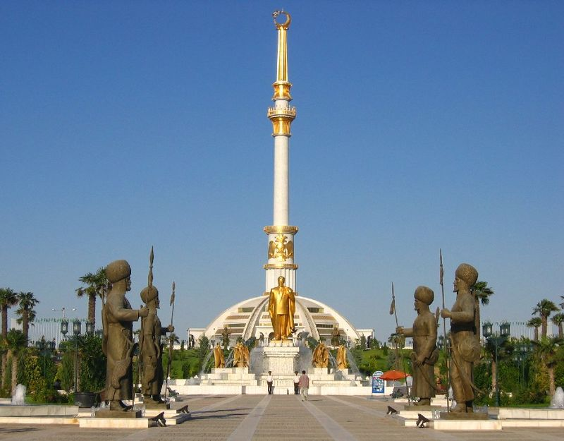 "The ""Independence Monument"" is a monument located in Ashgabat, Turkmenistan. The design of this building was inspired by traditional Turkmen tents and the traditional headgear worn by Turkmen girls. Elements of the building commemorate the independence date of Turkmenistan, 27 October 1991. These elements include a 91-meter reinforced concrete tower with a 27-metre high golden gilt steel construction on top of the tower, along with an observation terrace with a diameter of 10 metres. Within the building, there are exhibition halls where important works of art representing Turkmenistan history are displayed. The Monument of Independence sits on a total area of 84,500 m², surrounded by green landscaping that encompasses a cascaded pool and the statues of 27 historical heroes of the Turkmens that guided Turkmenistan history."