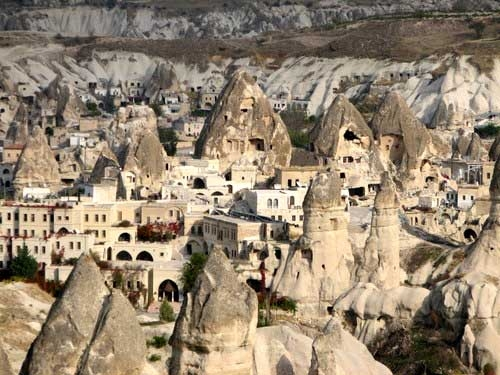 "is a village in Sahand Rural District, in the Central District of Osku County, East Azerbaijan Province, Iran. This village exemplifies manmade cliff dwellings which are still inhabited. The troglodyte homes, excavated inside volcanic rocks and tuffs similar to dwellings in the Turkish region of Cappadocia, are locally called ""Karaan"". Karaans were cut into the Lahars (volcanic mudflow or debris flow) of Mount Sahand. The cone form of the houses is the result of lahar flow consisting of porous round and angular pumice together with other volcanic particles that were positioned in a grey acidic matrix. After the eruption of Sahand these materials were naturally moved and formed the rocks of Kandovan. Around the village the thickness of this formation exceeds 100 m and with time due to water erosion the cone shaped cliffs were formed.[2] At the 2006 census, the village population was 601, in 168 families"