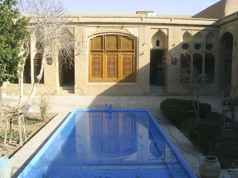 The150 year old Khan-e Lari, built in 19th century by Hadji Mohammad Ebrahim Lari, is one of the best-preserved Qajar-era houses in Yazd. The family used to use this building as a house for Darvishes of the Ne'mat-o-Allahi order in the past . The badgirs, traditional doors, stained-glass windows, elegant archways and alcoves mark it out as one of the city's grandest homes. The merchant family who built it have long gone, and it is now home to architecture students and cultural heritage officers. It has a charming atmosphere with a large pool in the central courtyard over which sits a huge, gently disintegrating wooden takht.
